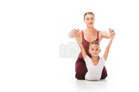 Foto de Entrenador femenino adulto atractivo ayudando a poco bailarina ejercicio aislado sobre fondo blanco - Imagen libre de derechos