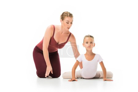 focused female trainer helping little ballerina stretching isolated on white background