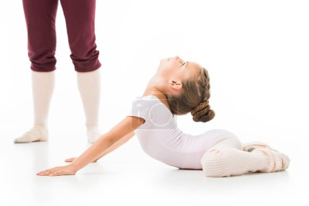 cropped image of female trainer in pointe shoes standing near little ballerina while she stretching isolated on white background