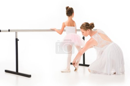 rear view of female teacher in tutu checking pointe shoes of little ballerina exercising at ballet barre stand isolated on white background
