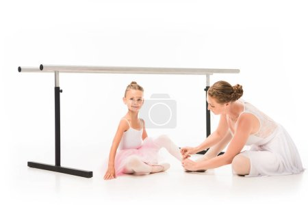 female trainer tying pointe shoes of little ballerina near ballet barre stand isolated on white background