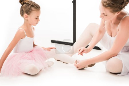adult female trainer pointing at pointe shoes of little ballerina near ballet barre stand isolated on white background