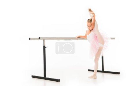 Photo pour Petite ballerine en jambe étirement tutu au ballet barre stand isolé sur fond blanc - image libre de droit