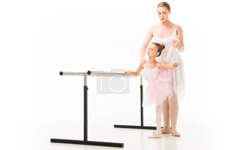 focused female teacher in tutu helping little ballerina practicing at ballet barre stand isolated on white background