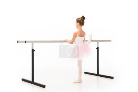 rear view of little ballerina in tutu and pointe shoes exercising at ballet barre stand isolated on white background