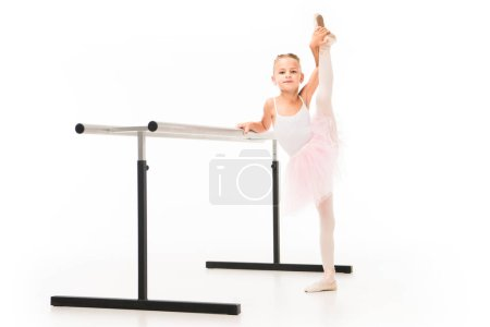 beautiful little ballerina in tutu and pointe shoes stretching at ballet barre stand isolated on white background