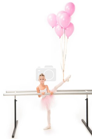 Photo pour Adorable petite ballerine en tutu pratique avec des ballons roses encapsulés sur elle au ballet barre stand isolé sur fond blanc - image libre de droit