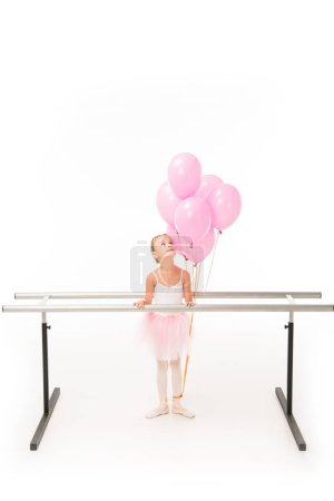 little ballerina in tutu standing at ballet barre stand and looking up at pink balloons isolated on white background
