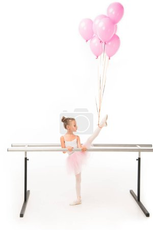 side view of little ballerina in tutu practicing with pink balloons wrapped over leg at ballet barre stand isolated on white background