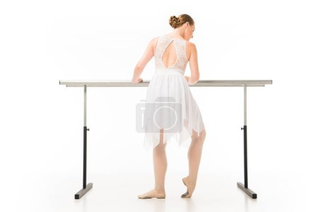 rear view of adult ballerina in tutu exercising at ballet barre stand isolated on white background