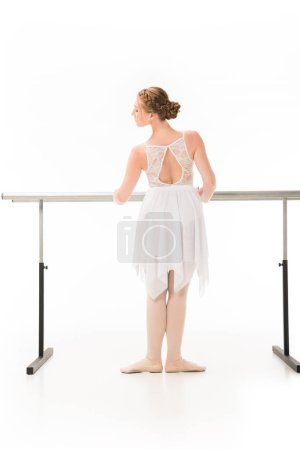 rear view of elegant ballerina in tutu and pointe shoes practicing at ballet barre stand isolated on white background