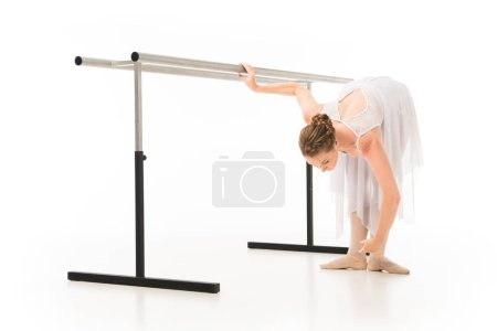 ballerina in tutu and pointe shoes practicing at ballet barre stand isolated on white background