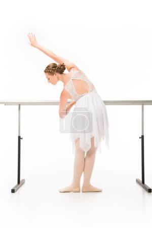 rear view of ballerina in tutu and pointe shoes practicing at ballet barre stand isolated on white background