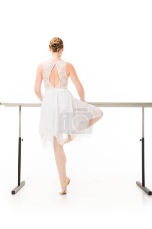 back view of ballerina in tutu and pointe shoes practicing at ballet barre stand isolated on white background