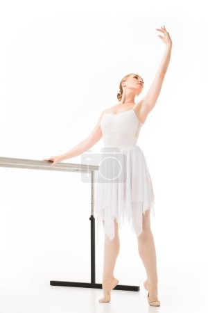 elegant ballerina in tutu and pointe shoes practicing at ballet barre stand isolated on white background
