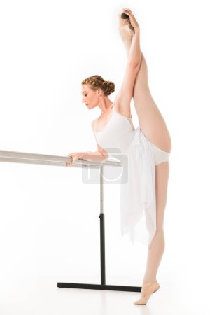 adult ballerina in tutu and pointe shoes stretching at ballet barre stand isolated on white background