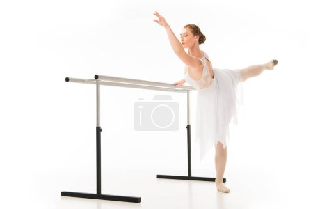 adult ballerina in tutu and pointe shoes exercising at ballet barre stand isolated on white background