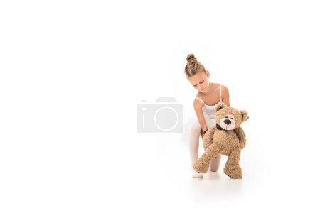 Foto de Pequeña bailarina en tutú sentado con oso de peluche aislado sobre fondo blanco - Imagen libre de derechos