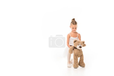 Photo for Happy little ballerina in tutu sitting with teddy bear isolated on white background - Royalty Free Image