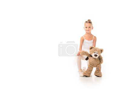 Photo for Adorable little ballerina in tutu sitting with teddy bear isolated on white background - Royalty Free Image