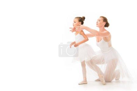 Photo pour Adulte femme formatrice en tutu aider petite ballerine exercice isolé sur fond blanc - image libre de droit