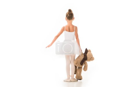 rear view of little ballerina in tutu practicing with teddy bear isolated on white background