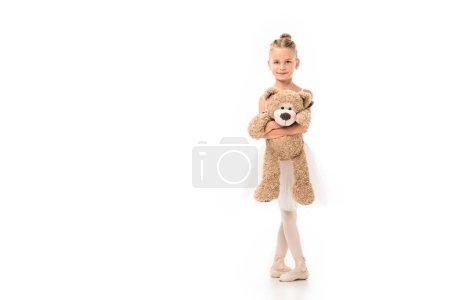 Foto de Sonriente bailarina poco en pie de tutú con oso de peluche aislado sobre fondo blanco - Imagen libre de derechos