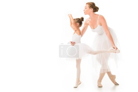 Photo pour Vue latérale de l'entraîneur féminin adulte en tutu aidant petite ballerine exercice isolé sur fond blanc - image libre de droit