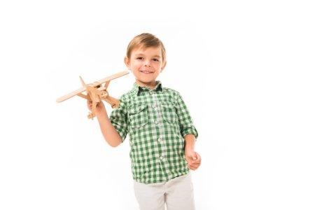 Photo pour Gai petit garçon jouer avec jouet en bois avion isolé sur fond blanc - image libre de droit