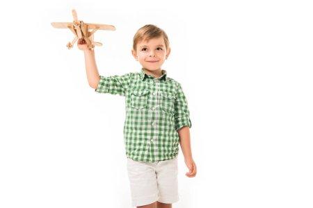 Photo pour Heureux petit garçon jouer avec jouet en bois avion isolé sur fond blanc - image libre de droit