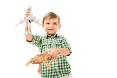 Photo for Smiling little boy playing with toy planes isolated on white background - Royalty Free Image