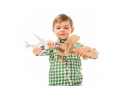 adorable little boy playing with toy planes isolated on white background