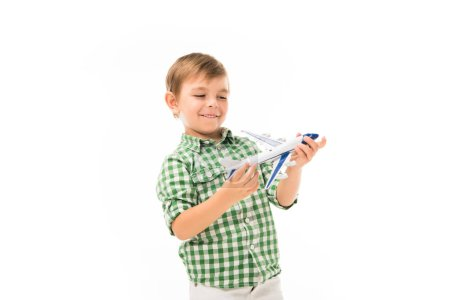 smiling little boy playing with toy plane isolated on white background