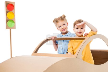 siblings playing with cardboard car and traffic lights, isolated on white