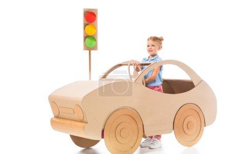 stylish female preschooler driving cardboard car on white with traffic lights