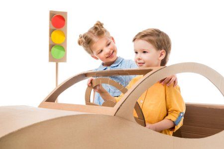 smiling kids playing with cardboard car and traffic lights, isolated on white