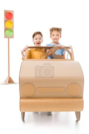 excited adorable children driving cardboard car with traffic lights on background, on white