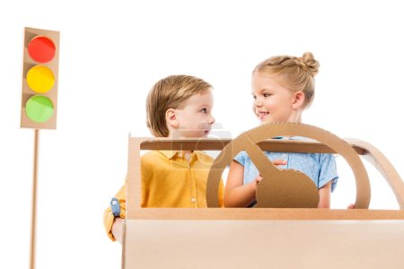adorable children driving cardboard car with traffic lights on background, isolated on white