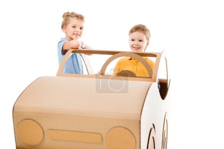 adorable kids playing with cardboard car, isolated on white