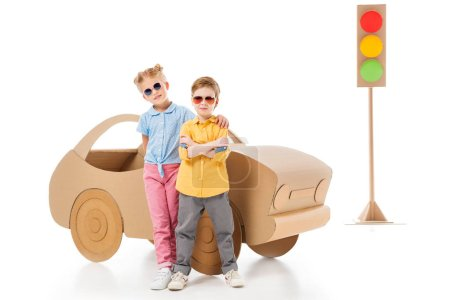 stylish kids in sunglasses posing near cardboard car and traffic lights, on white