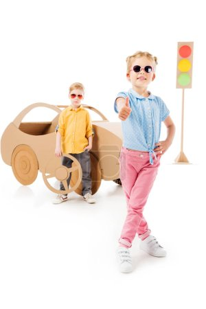 stylish kid in sunglasses showing thumb up while boy standing near cardboard car and traffic lights, on white