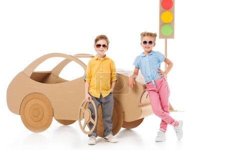 stylish children in sunglasses posing near cardboard car and traffic lights, on white