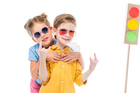 stylish children in sunglasses, boy showing rock n roll signs, isolated on white with cardboard traffic lights on background
