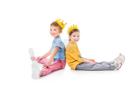 Photo for Smiling friends in yellow paper crowns sitting back to back, isolated on white - Royalty Free Image