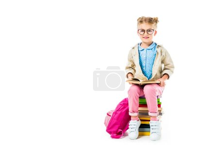 adorable pupil reading while sitting on pile of books with pink backpack isolated on white