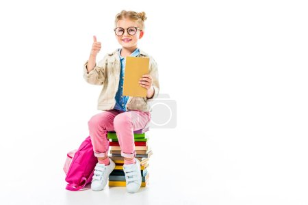 adorable smiling pupil showing thumb up while sitting on pile of books isolated on white, knowledge concept