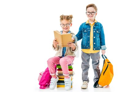 schoolchildren in eyeglasses studying and sitting on books with backpacks, isolated on white