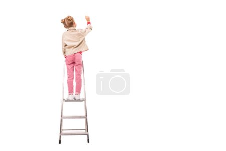 rear view of schoolchild standing on ladder and writing isolated on white