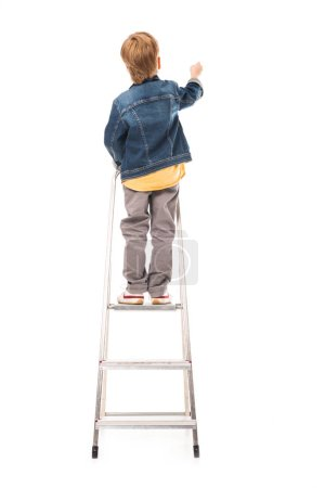 rear view of pupil standing on ladder and writing isolated on white