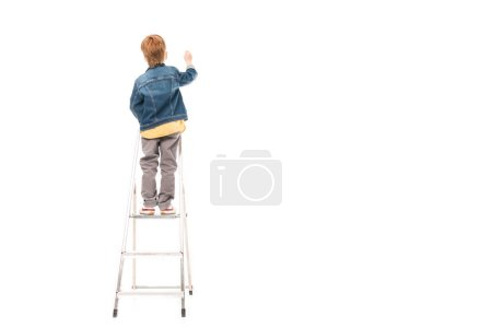 back view of schoolboy standing on ladder and writing isolated on white